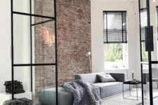 a minimalist living room with a brick wall, a grey sofa, a black coffee table and black shades
