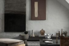 a minimalist living room with a wabi-sabi feel, with a stone floor and concrete walls, minimal furniture and artworks