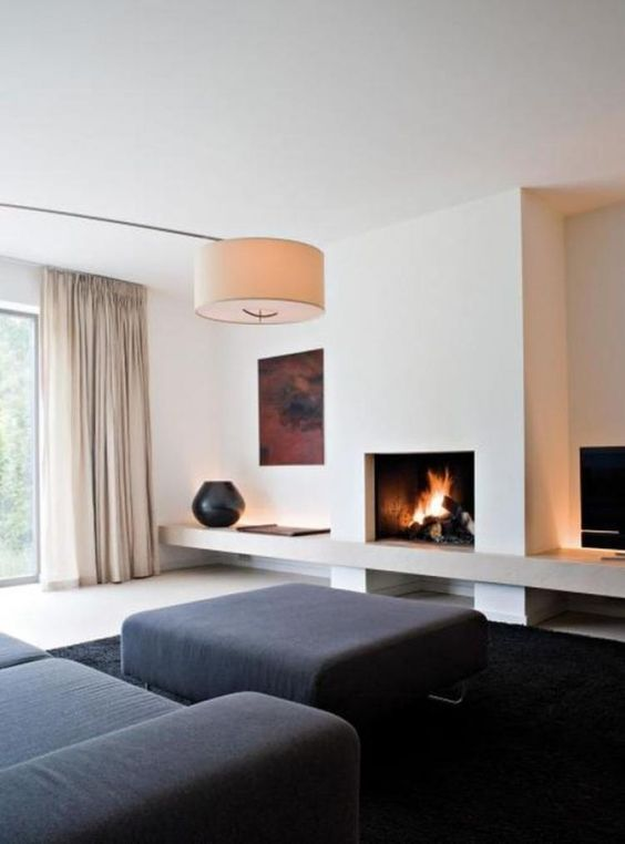 a minimalist living room with black furniture and a rug, a fireplace, an artwork, a lamp and neutral curtains