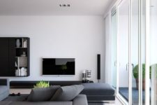 a minimalist living room with grey furniture, a TV, a wall-mounted storage unit and a glazed wall for much natural light
