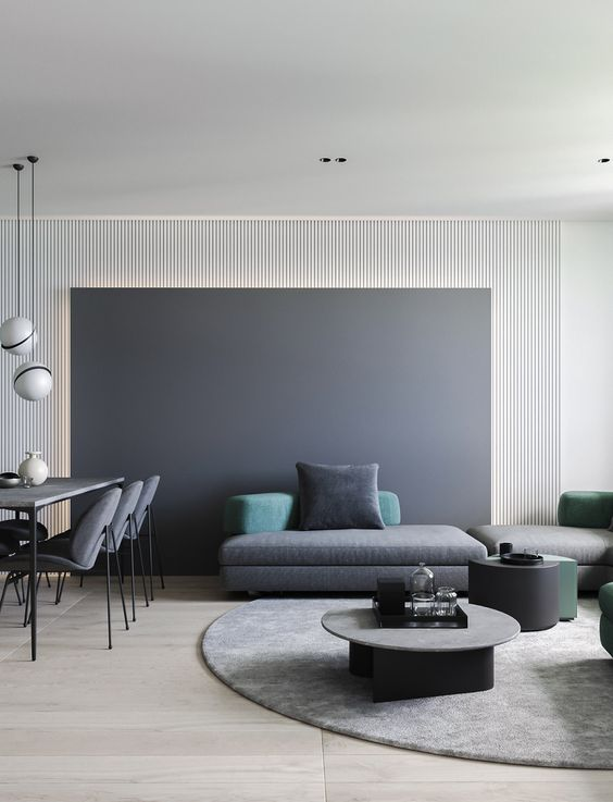 a minimalist living space with a chalkboard wall, dark coffee tables, a grey sectional sofa plus colored pillows