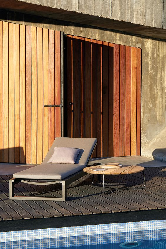 a minimalist lounger with dark metal framing and taupe upholstery with pillows is a nice fit for a modern or minimalist space