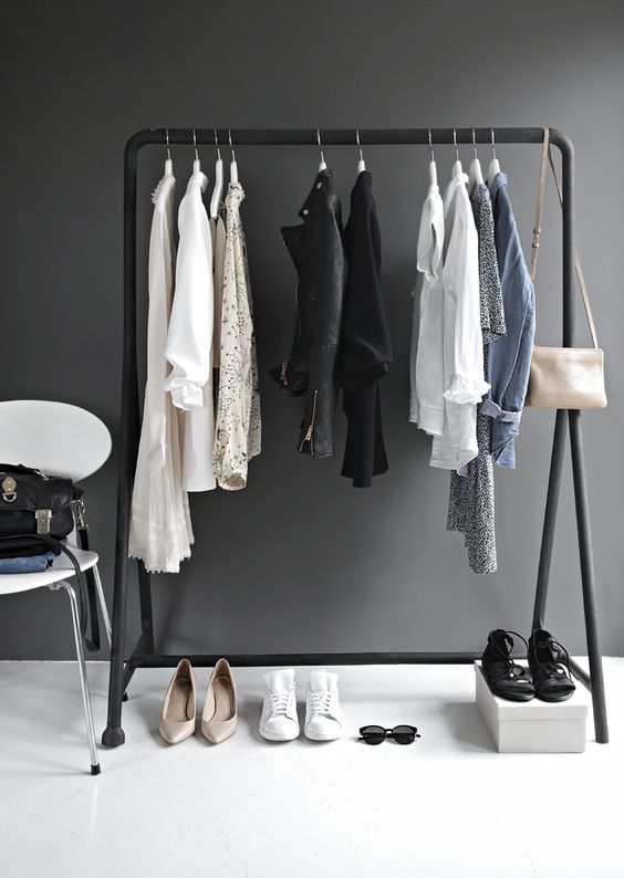 a minimalist makeshift closet done with a black frame, a white chair and a box for shoes