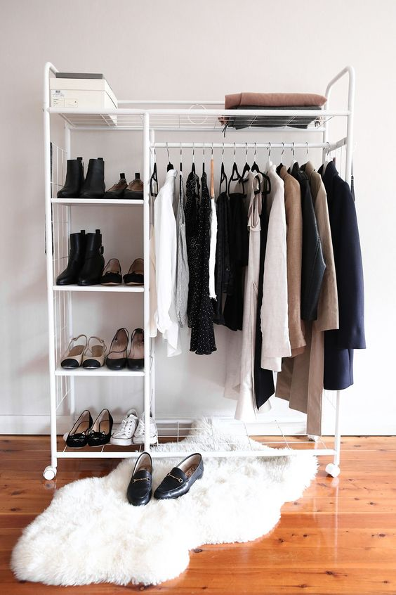 a minimalist makeshift closet with shoe shelves, a box and some space for clothes hangers