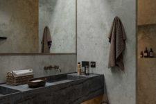 a minimalist meets wabi-sabi bathroom with concrete walls, a stone vanity and a basket for storage