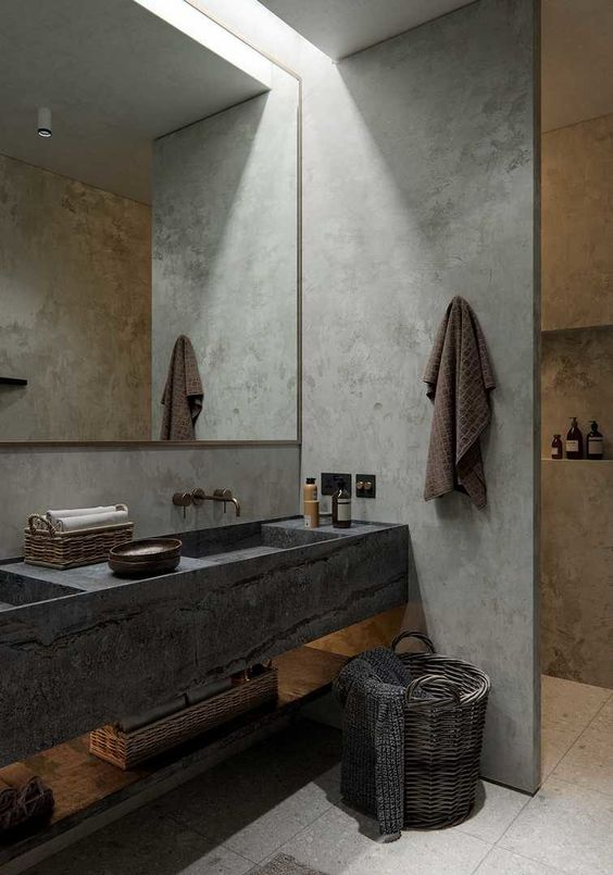 a minimalist meets wabi-sabi bathroom with concrete walls, a stone vanity and a basket for storage