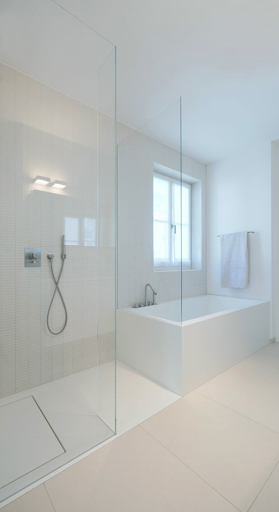 a minimalist neutral bathroom with largre scale and skinny tiles, a glass enclosed shower and a soak tub