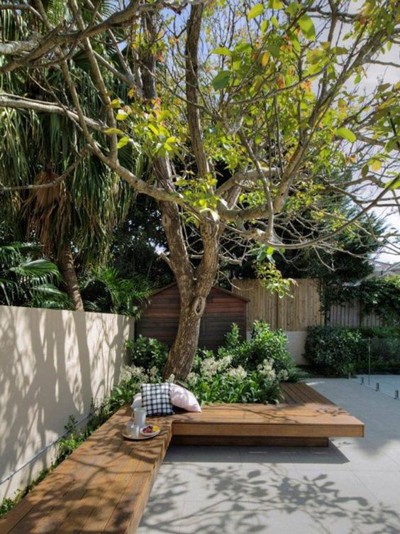 a minimalist terrace clad with concrete tiles, with a built-in bench, some greenery and trees growing here is a lovely space to have a rest