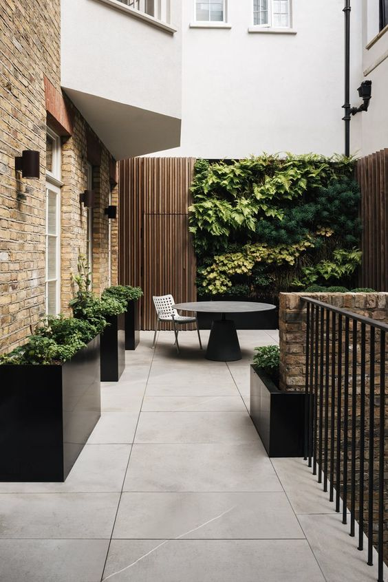 a minimalist terrace clad with large scale tiles, black planters with greenery, a black round table, a living wall that makes a statement
