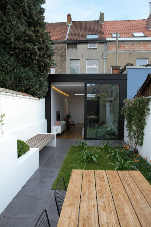 a minimalist terrace clad with tiles, built-in bnches and potted greenery and blooms, a planked woodne table and metal chairs