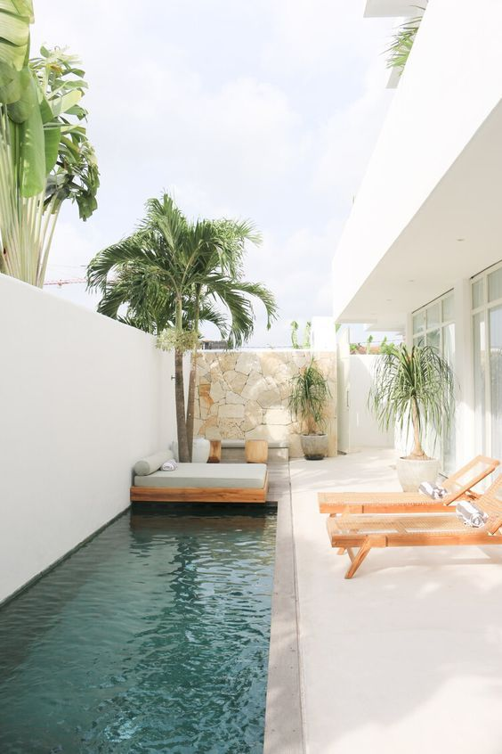 a minimalist terrace wiht a stone clad wall, wooden loungers, a daybed with a grey mattress with pillows, trees and a long pool