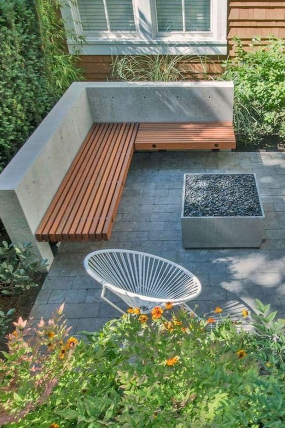 a minimalist terrace with concrete tiles, a built-in corner bench, a fire pit, a round chair and lots of greenery and blooms around
