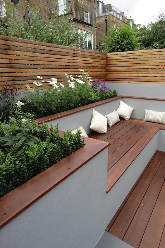 a minimalist terrace with rich-stained wood, built-in benches, potted blooms and greenery and plank wood screens around