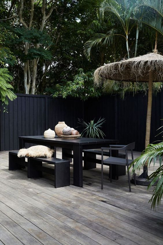 a minimalist tropical terrace with a reclaimed wooden deck, laconic black dining set and a tall umbrella plus vases on the table
