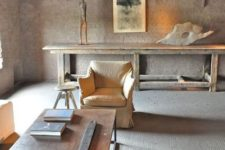 a minimalist wabi-sabi living room in neutrals with brick walls, a concrete floor and rough and brutal furniture