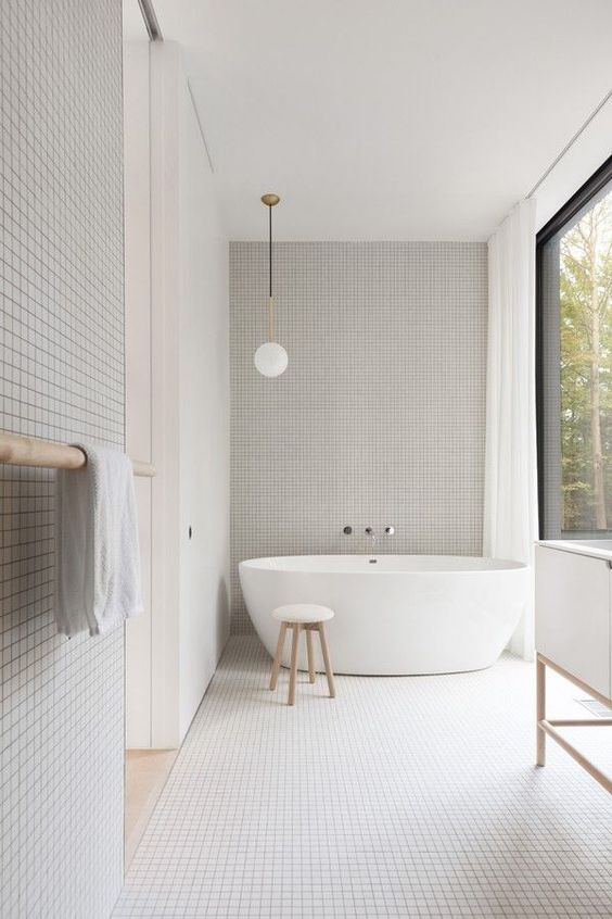 a minimalist white bathroom all clad with small white tiles, a glazed wall and white appliances