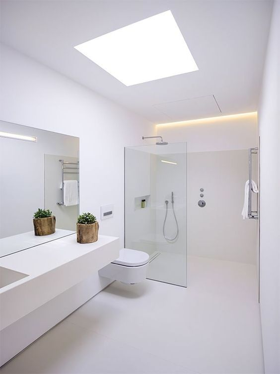 a minimalist white bathroom with a skylight and built-in lights, a sleek vanity, a shower with a glass partition and white appliances