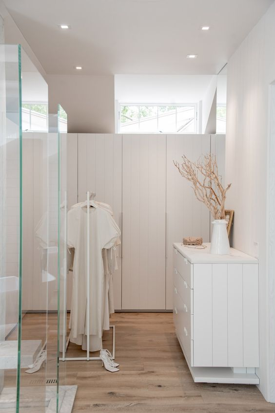 a minimalist white closet done with sleek wardrobes, a dresser that matches and a makeshift part plus glass doors