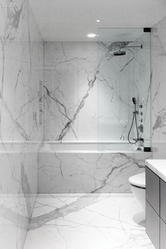 a minimalist white marble bathroom with a black vanity, white appliances and simple fixtures