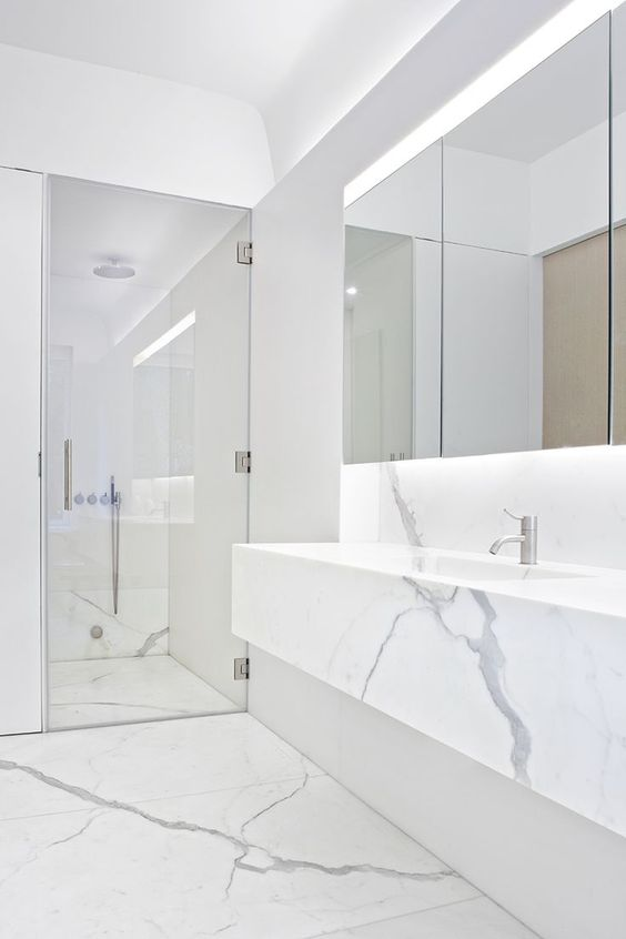 a minimalist white marble bathroom with a shower space, a floatign vanity, a statement mirror and built-in lights