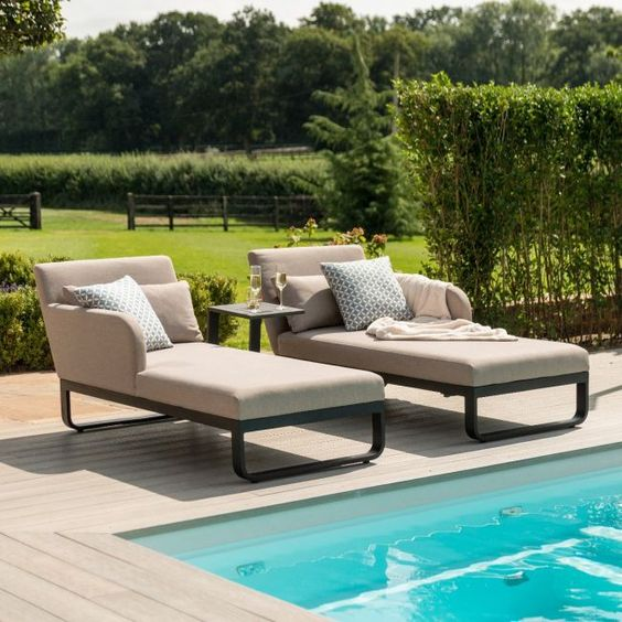 a modern lounger with metal framing and very comfy upholstery, a black and an armholder plus pillows for maximal coziness