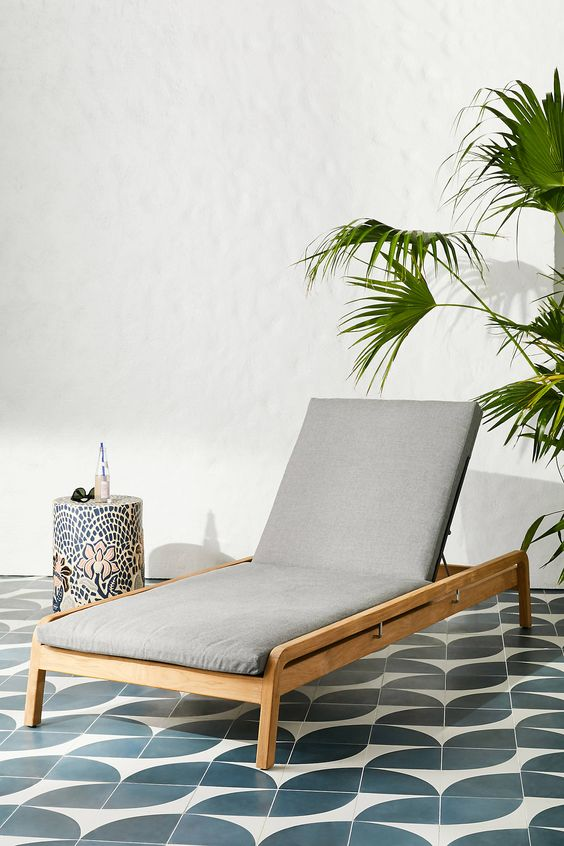 a modern neutral wood lounger with grey upholstery is a stylish and cool idea for a modern outdoor space