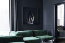a moody graphite grey living room with a small coffeee tables, an emerald grene sectional sofa and a statement artwork