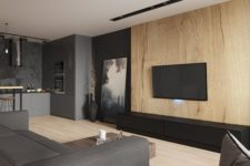 a moody minimalist living room with a wooden wall, a grey sofa, dark touches and an artwork plus a TV on the wall