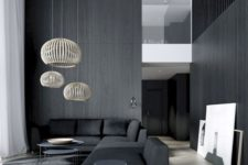 a moody minimalist living room with black walls and a sectional sofa, rattan lampshades and a couple of coffee tables