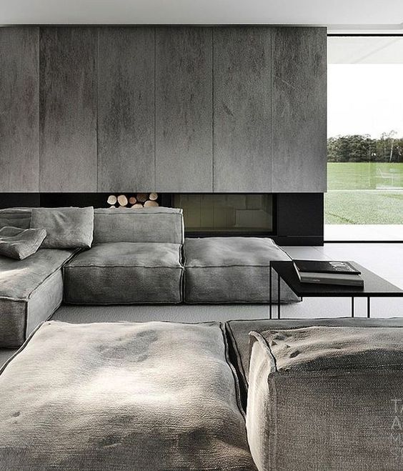 a moody minimalist living space with grey panels, a built-in fireplace, grey canvas furniture and black touches