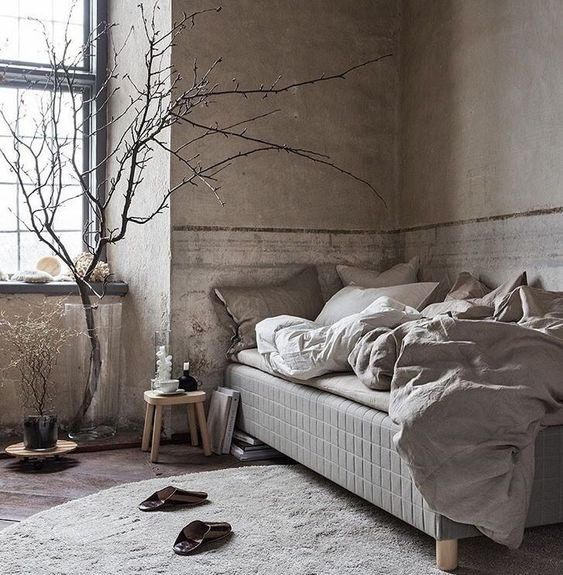 a neutral brutal interior with concrete walls, a wooden floor and some very simple yet comfortable furniture