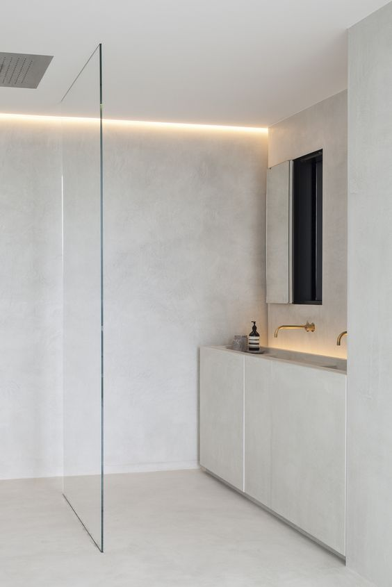 a neutral minimalist bathroom with built-in lights, a shower with a glass partition and a vanity with two sinks built-in
