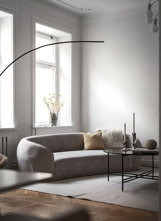 a neutral minimalist living room with a curved sofa, a pendant lamp, a coffee table, pillows and blooms in a vase