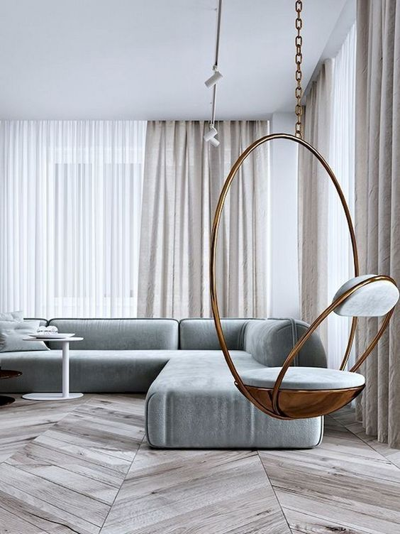 a neutral minimalist living room with off-white curtains, a grey sectional sofa, a hanging copper chair and a laconic coffee table