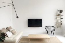 a neutral minimalist living room with off-white cushions, wooden furniture, a TV on the wall and a wall lamp