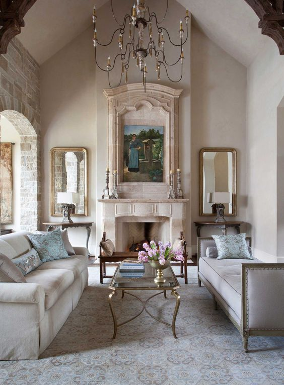 a neutral vintage living room with a fireplace, a refined chandelier, two mirrors, a couple of sofas and a glass table