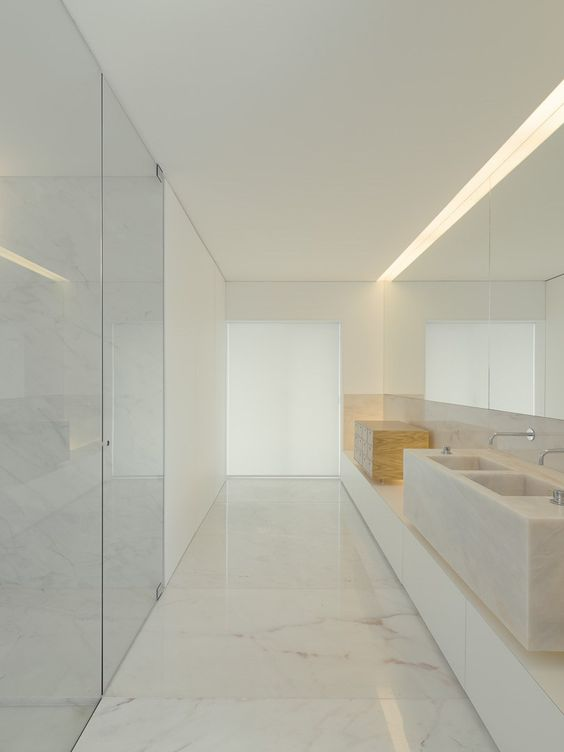 a pure minimalist bathroom done with white marble, a floating vanity, a stone slab sink and a shower clad with glass