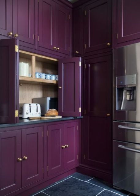a purple kitchen with a cabinet with folding doors and some appliances hidden there plus some mugs to make breakfast
