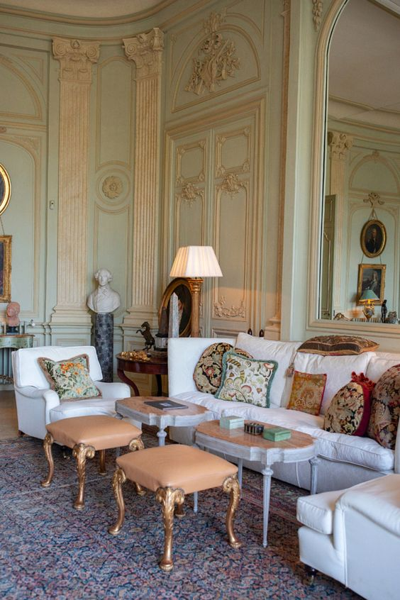 a refined Provence living room with light green and gold walls, chic and beautiful furniture, table lamps and statuettes