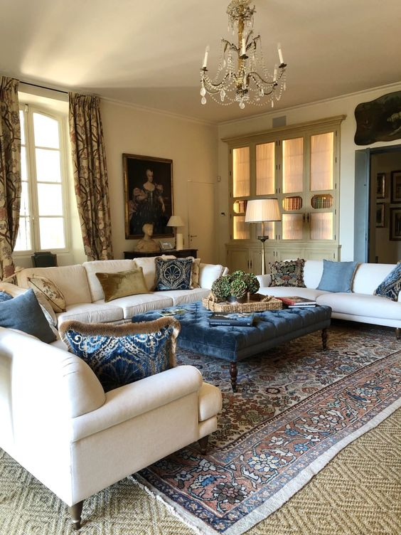 a refined and chic Provence living room with neutral furniture, a crystal chandelier, printed textiles and a beautiful artwork