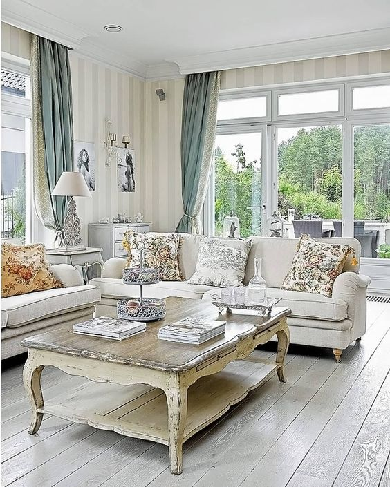 a refined vintage living room with chic neutral furniture, a low coffee table, striped walls and two color curtains plus floral pillows