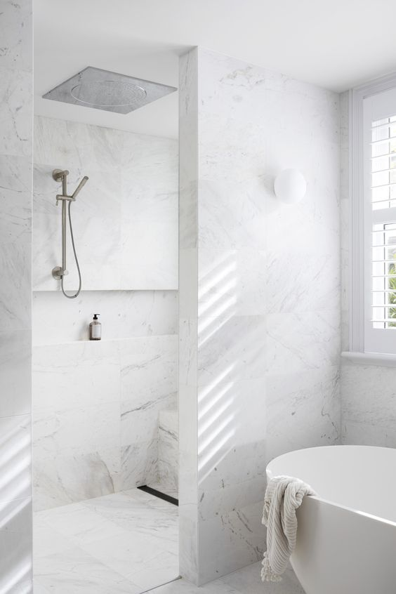 a refined white marble minimalist bathroom with a shower and bathtub space and windows is airy and serene