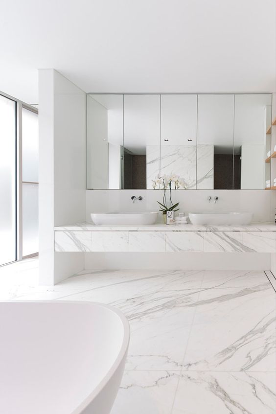 a refined white minimalist bathroom with white marble tiles on the floor and a white marble vanity, white appliances and a mirror wall