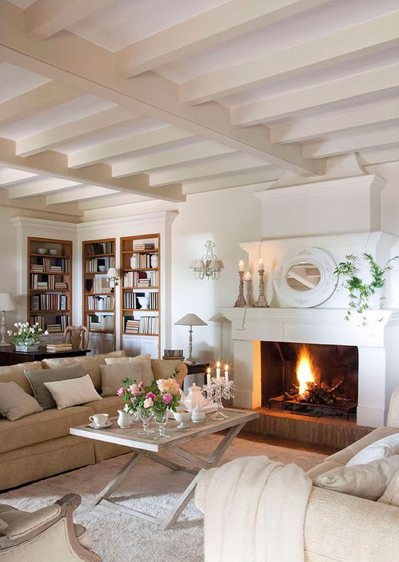 a romantic Provence living room with a fireplace, neutral furniture and a trestle table, candleholders and a mirror on the mantel
