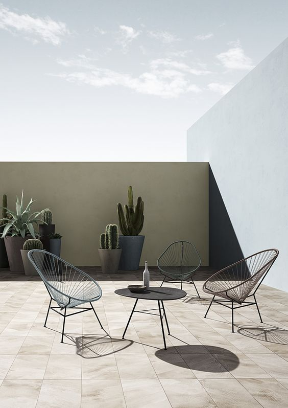 a simple and minimal terrace with a tan wall, several chairs, a sculptural table and tall planters with succulents and cacti