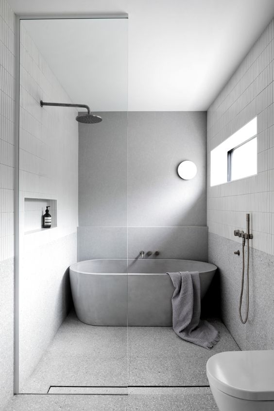 a simple minimalist bathroom clad with skinny white tiles and grey stone-like ones, a concrete tub, white appliances