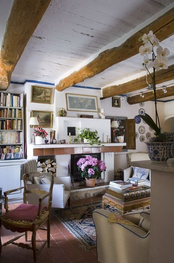 a small Provence living room with a fireplace, wooden beams, neutral furniture and stacked books plus decorative plates