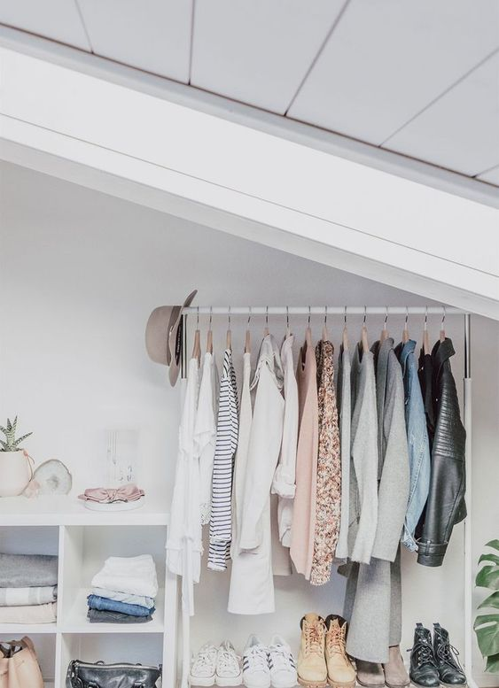 a small attic closet in white, with a makeshift closet, a shoe shelf and an open storage unit plus some plants
