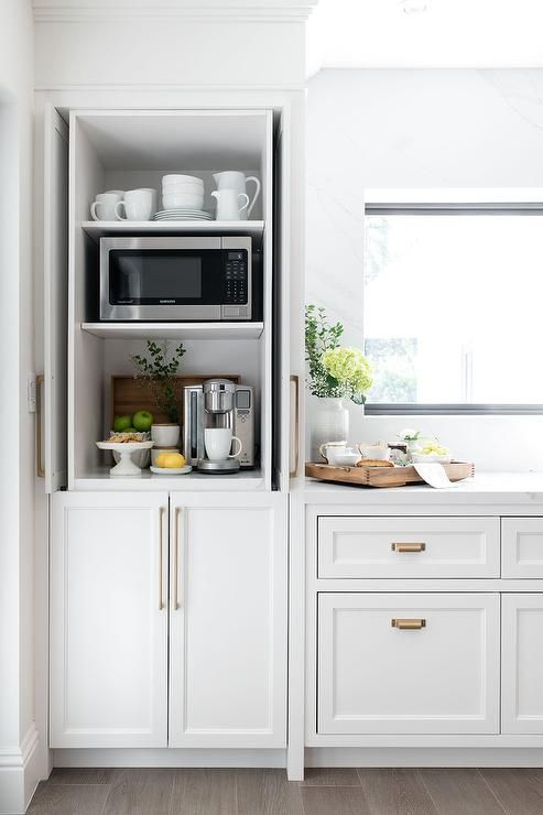 a small cabinet with mugs, jugs and cups, a mini coffee station with fruits and cookies and a microwave is a cool idea