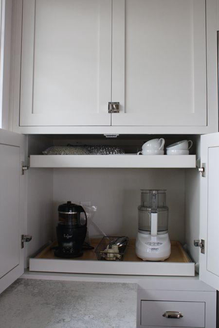 a small cabinet with retractable shelves that hold appliances and mugs is a cool idea to make your own tea and coffee station hidden